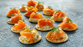 Smoked Salmon and soft chees canapes appetizers with chives on stone table Stock Images