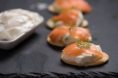 Smoked Salmon and soft chees canapes appetizers. With chives on black table Royalty Free Stock Photo