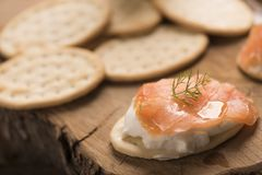 Smoked Salmon and soft chees canapes appetizers. On wooden chopping board Stock Images