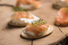 Smoked Salmon and soft chees canapes appetizers. On wooden chopping board Stock Photography