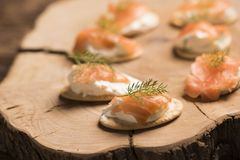 Smoked Salmon and soft chees canapes appetizers. On wooden chopping board Royalty Free Stock Photography