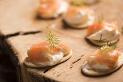 Smoked Salmon and soft chees canapes appetizers. On wooden chopping board Royalty Free Stock Images