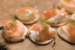 Smoked Salmon and soft chees canapes appetizers. On wooden chopping board Royalty Free Stock Photos
