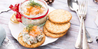 Smoked salmon, soft cheese and dill spread. Mousse, pate, rillette in a jar with crackers on white wooden background. Delicious Christmas themed dinner table Stock Photo