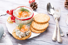 Smoked salmon, soft cheese and dill spread. Mousse, pate, rillette in a jar with crackers on white wooden background. Delicious Christmas themed dinner table Stock Photography