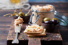 Smoked salmon and soft cheese spread, mousse, pate in a jar with crackers and capers on a wooden background Royalty Free Stock Images