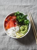 Smoked salmon sushi bowl on grey background, top view. Rice, avocado puree, salmon - healthy food concept. Royalty Free Stock Images