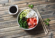 Smoked salmon sushi bowl on wooden background, top view. Rice, avocado puree, salmon - healthy food Stock Photo