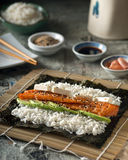 Smoked Salmon Sushi Roll. A delicious smoked salmon sushi roll with avocado, cream cheese, and roasted sesame seeds Royalty Free Stock Photography