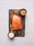 Smoked salmon on vintage cutting board with salt and pepper on wooden rustic background top view Royalty Free Stock Image
