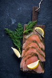 Smoked salmon on wooden board with dil and lemon Royalty Free Stock Photos