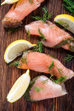 Smoked salmon on wooden board with dil and lemon Royalty Free Stock Photography