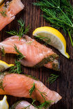 Smoked salmon on wooden board with dil and lemon Stock Photo