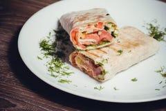 Smoked salmon wrap with vegetables. On white plate stock photos