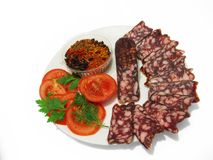 Smoked sausage. On a plate with tomatoes herbs and spices royalty free stock photos