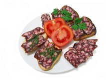 Smoked sausage. Surrounded by tomatoes, sandwiches with sausage and greens royalty free stock photos
