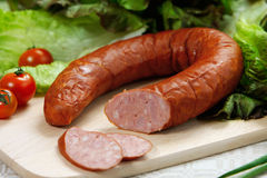 Smoked sausage. On wooden cutting board Stock Images