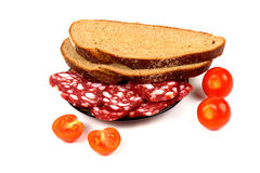 Smoked sausage, cherry tomatoes and bread on a white Stock Images