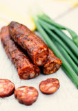Smoked sausage. Delicious smoked sausage and spring onion on wooden   table Royalty Free Stock Photos
