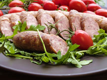 Smoked sausage with greens and tomatoes. On round plate Stock Images