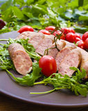 Smoked sausage with greens and tomatoes. On round plate Royalty Free Stock Photography