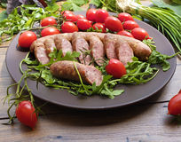 Smoked sausage with greens and tomatoes. On round plate Stock Photo