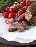 Smoked sausage with greens and tomatoes. On round plate Stock Photography