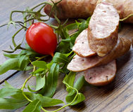 Smoked sausage with greens and tomatoes on wood Stock Images