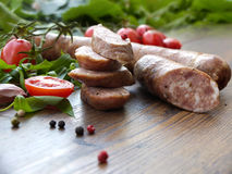 Smoked sausage with greens and tomatoes on wood Stock Photography