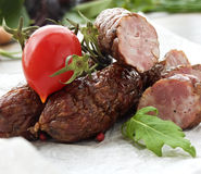 Smoked sausage with greens and tomatoes on wood Stock Photos