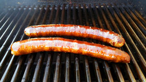 Smoked sausage on the grill. Two smoked sausage on the grill cooking up slow Royalty Free Stock Image