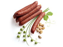 Smoked sausage with onion, green pea and pistachio. Smoked sausage decorated with onion, green pea and pistachio over white background Stock Photos