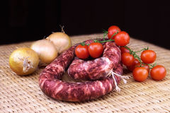 Smoked sausage with onions and a bunch of small red tomatoes Royalty Free Stock Photo