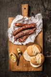 Smoked  sausage in paper on  cutting board , dark wooden background Royalty Free Stock Photo