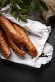 Smoked sausage in paper on a kitchen dark worktop. stock photography
