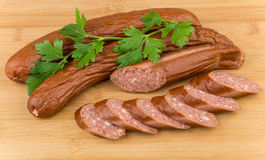 Smoked sausage and parsley on board Stock Images