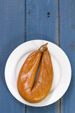Smoked sausage on plate. On blue background Royalty Free Stock Photos