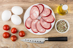Smoked sausage in plate, tomatoes, eggs, spices, vegetable oil Royalty Free Stock Photography