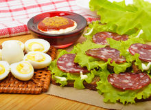 Smoked sausage with quail egg, lettuce Stock Photography