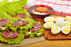Smoked sausage with quail eggs and lettuc Royalty Free Stock Images