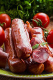 Smoked sausage and red ripe tomatoe. S on the kitchen table, selective focus Stock Photos