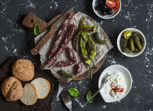 Smoked sausage, roasted peppers, olives, cheese and gherkins on a dark background. Delicious snack Stock Photos