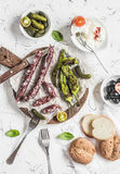 Smoked sausage, roasted peppers, olives, cheese and gherkins on a light background. Delicious snack Royalty Free Stock Photography