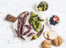 Smoked sausage, roasted peppers, olives and gherkins on a light background. Delicious snack Royalty Free Stock Images