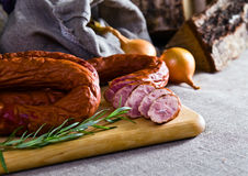 Smoked sausage. And rosemary on a linen cloth Stock Images