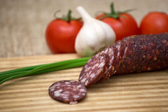 Smoked sausage with rustic food. On wooden board Stock Photos