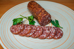 Smoked sausage salami sliced on a plate with greens Stock Photos