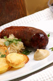 Smoked sausage with sauerkraut and potato Royalty Free Stock Photos