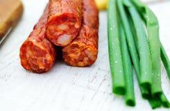 Smoked sausage. Spicy smoked sausage and spring onion Royalty Free Stock Photography