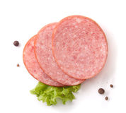 Smoked sausage. Three pieces pf smoked sausage with fresh green lettuce and black pepper on the white Stock Photography